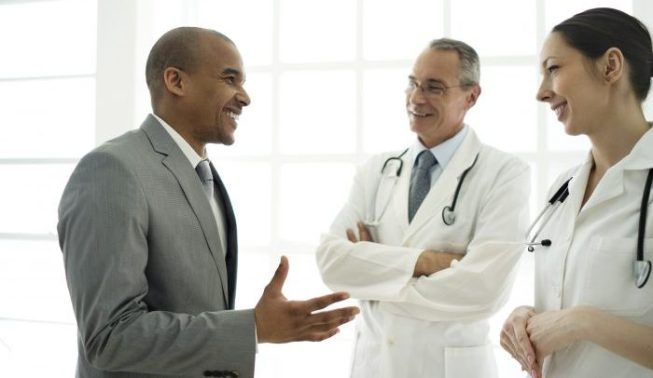 Happy African American businessman standing and discussing with young female and mature male doctor.