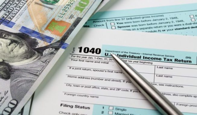 Filling out income tax forms with US dollar and pen