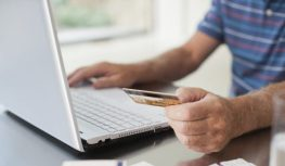 Close up of man using credit card to purchase merchandise online